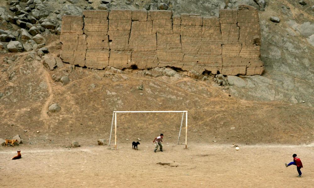 Chlapci hrají fotbal v areálu archeologických vykopávek v Limě, Peru