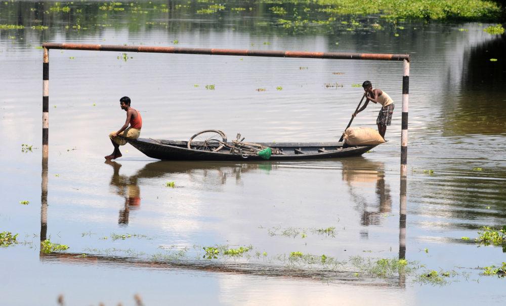 Místní obyvatelé plují mimo zatopené fotbalové brány v Indii