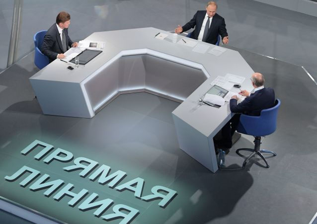 Vladimir Putin spolu s moderátory během Přímé linky