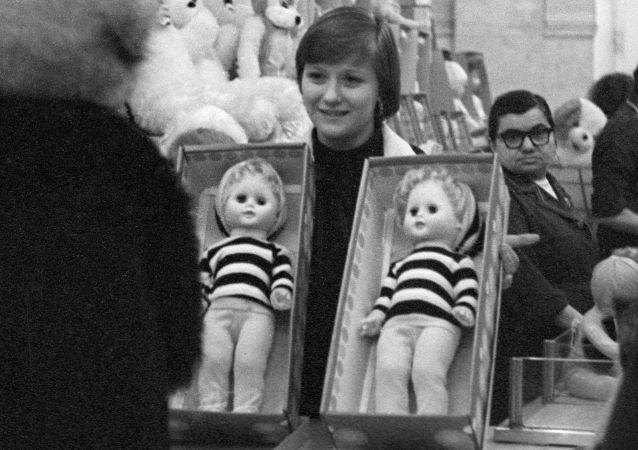 Prodavačka obchodního domu Dětský mír nabízí panenky na výběr, 1979