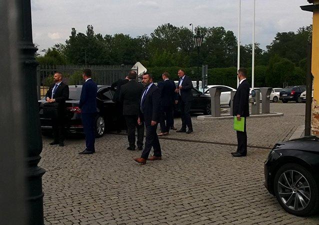 Z tmavých vozů vystupují muži prezidentova kruhu, aby doprovodili hlavu státu k mikrofonu