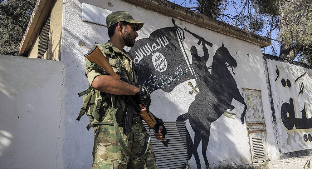 A Free Syrian Army fighter stands in front of a painting left by IS militants in Jarablus, Syria (File)