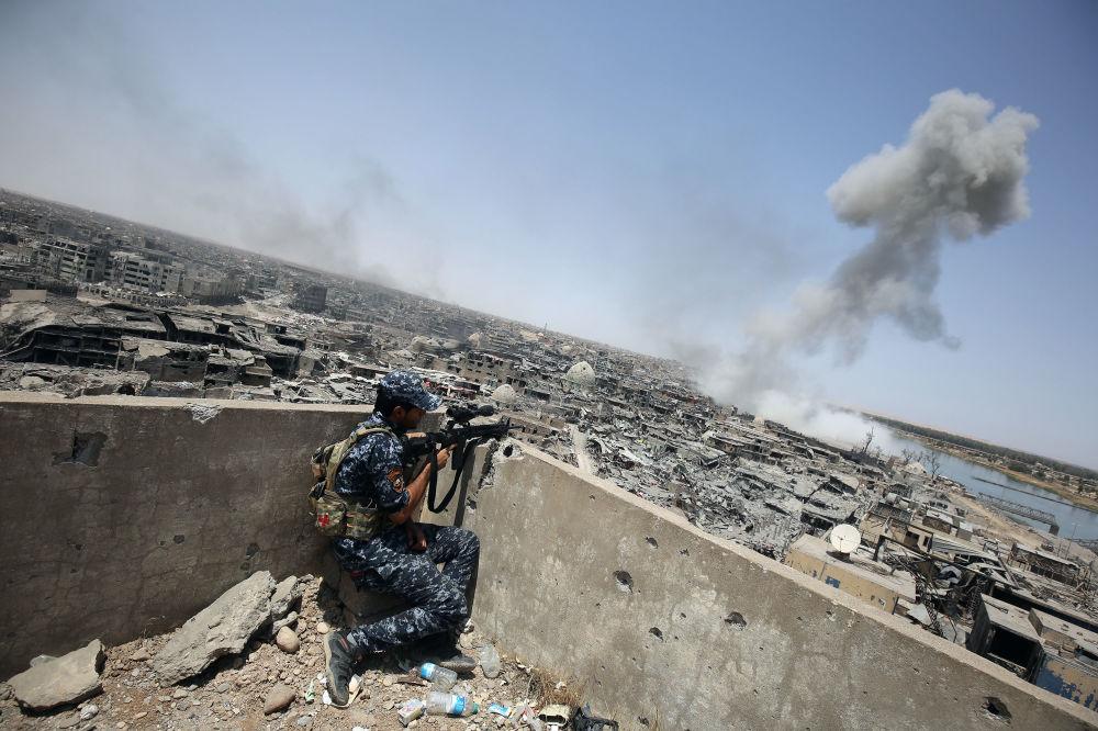 Irácký ostřelovač pozoruje letecké údery mezinárodních koaličních sil pod vedením Spojených států, zaměřených na ISIS, ve starém městě Mosulu, červenec 2017
