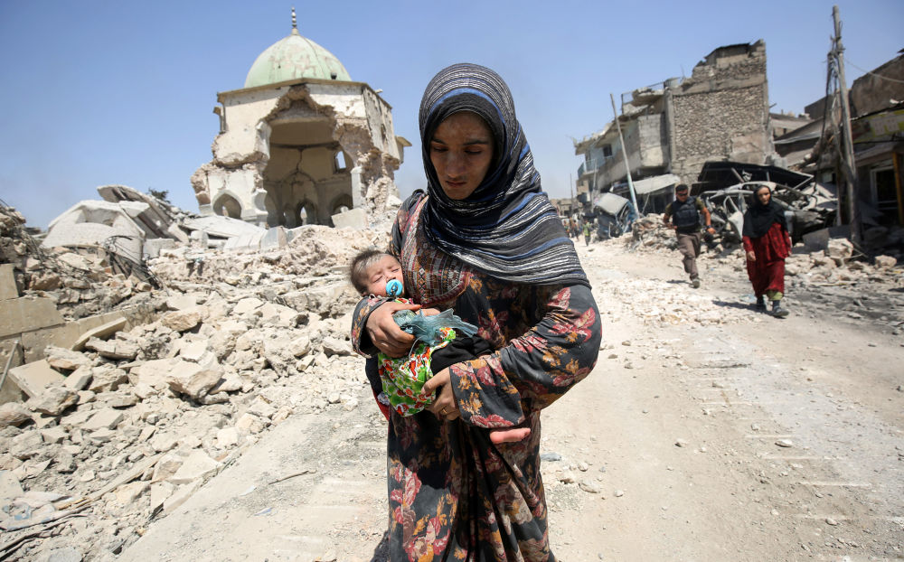 Írácká žena s dítětem před zničenou mešitou Al-Nuri v Mosulu v červenci 2017
