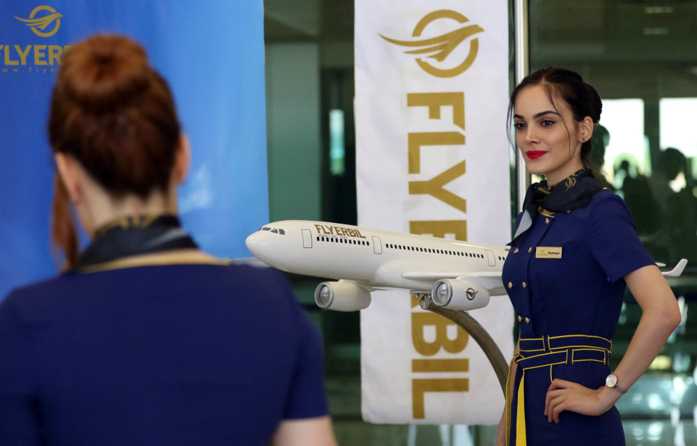 Letuška aerolinek Fly Erbil pózuje u makety letadla na mezinárodním letišti v Erbilu, Irák.