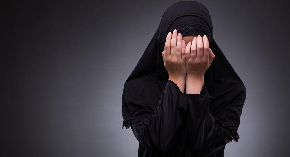 Muslimka zakrývá obličej rukama