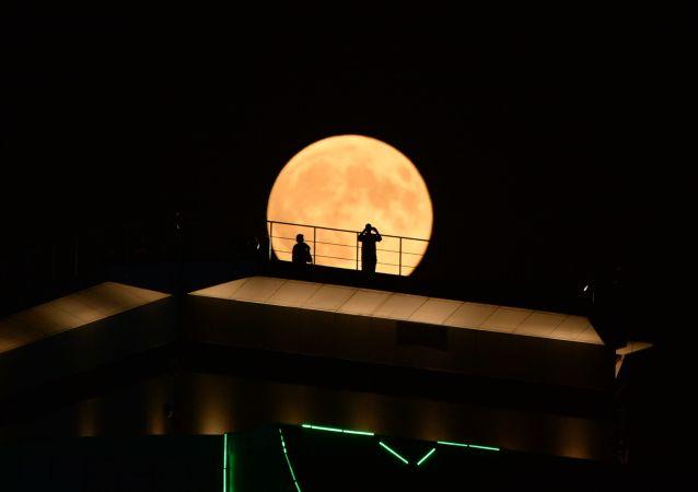Měsíc během zatmění na pozadí mrakodrapu Groznyj City v Čečně