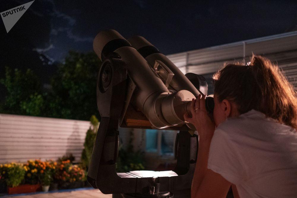 Dívka pozoruje úplné zatmění měsíce v observatoři Kubanské státní univerzity