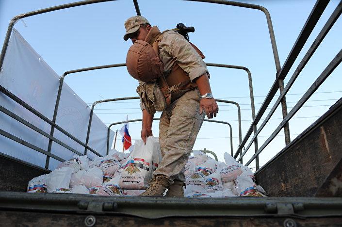 Ruský voják rozdává humanitární pomoc syrským civilistům