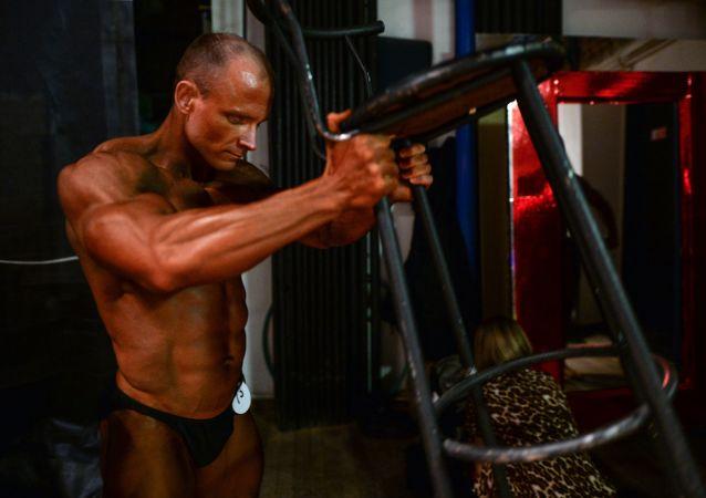 Účastník šampionátu Sibiře v bodybuildingu, fitnessu a bodyfitnessu se připravuje na vystoupení