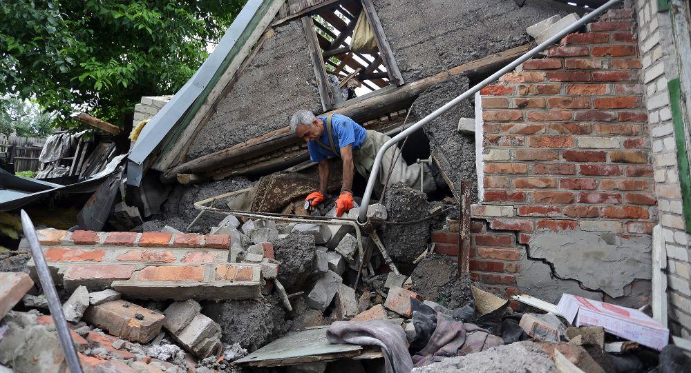 Záchranář se snaží najít ženu pod troskami jejího domu nedaleko Horlivky. Archivní foto