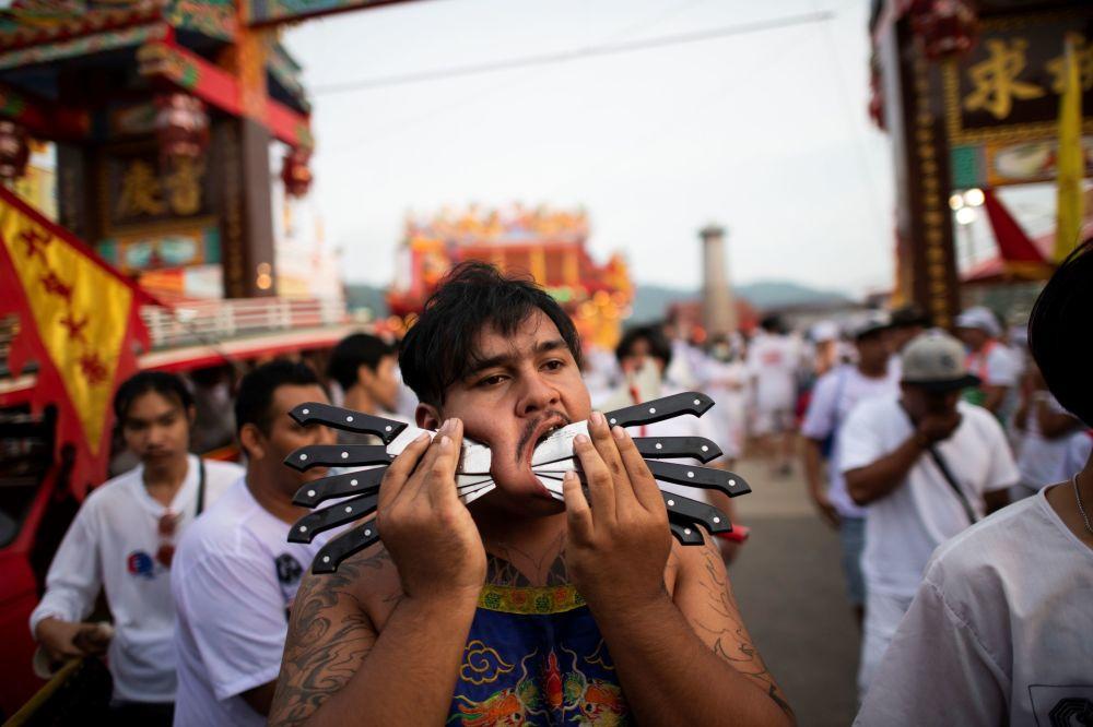Jeden z účastníků festivalu, který má své tváře propíchnuté několika noži.