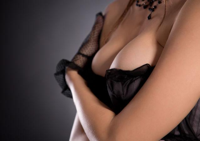 Dámská prsa v černém korzetu