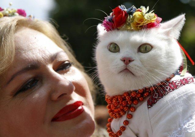 Ukrajinka a její kočka v ukrajinských lidových krojích. Archivní foto