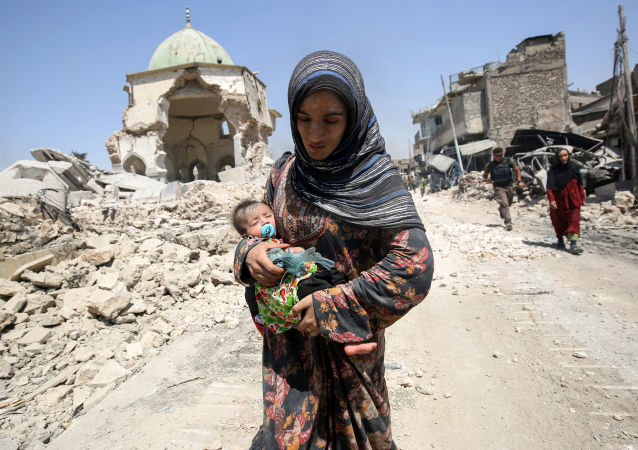 Iráčanka s dítětem naproti zničené mešitě v Mosulu