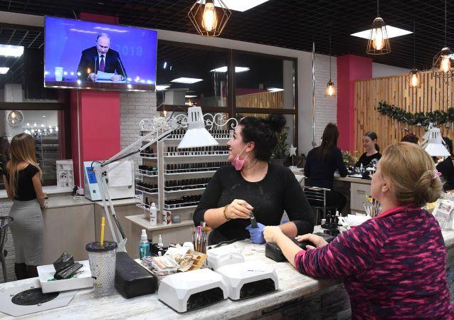 Ženy sledují přímý přenos každoroční velké tiskové konference ruského prezidenta Vladimira Putina v kosmetickém salonu ve Vladivostoku.