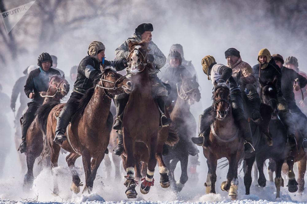 Účastníci národního jezdeckého sportu Alaman Ulak na území obce Dača SU poblíž Biškeku