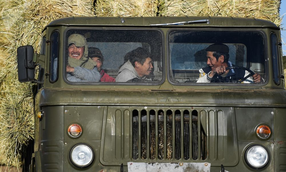 Pracovníci v kabině kamionu při sběru sena v mongolské stepi