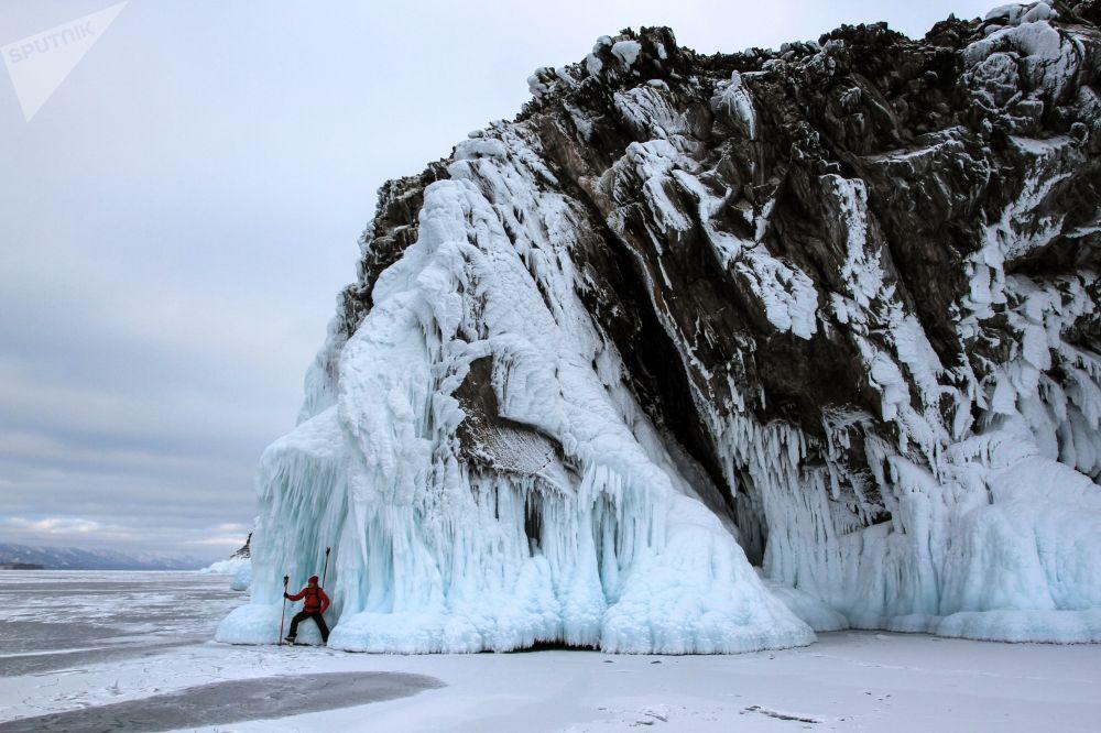 Turista, který bruslí na zamrzlém břehu Bajkalu.