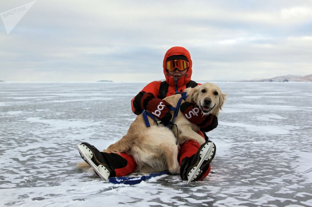 Jeden z turistů spolu se svým psem na zamrzlém jezeře Bajkal.