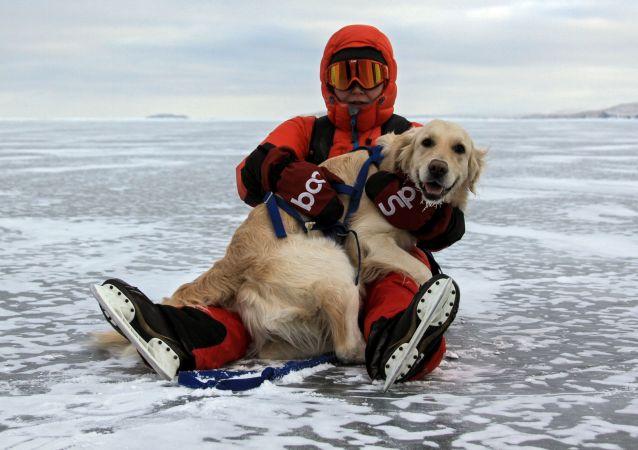 Jeden z turistů spolu se svým psem na zamrzlém jezeře Bajkal