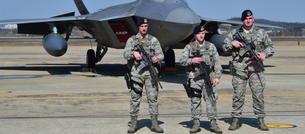 Američtí vojáci na pozadí stíhačky F-22 na vojenské základně v Jižní Koreji