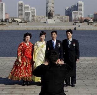 Rodina, která pózuje na svatebních fotografiích. V pozadí je vidět Památník ideologie Čučche (Juche Tower), který se nachází v Pchjongjangu.