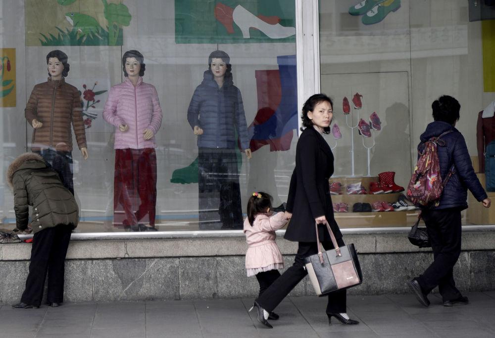 Lidé chodí kolem výlohy jednoho z obchodů v centru Pchjongjangu, Severní Korea.