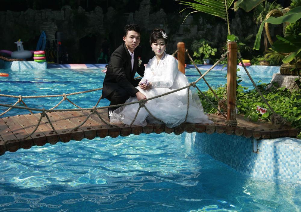 Novomanželé pózující na svatební fotografii v krytém bazénu v Pchjongjangu, KLDR.