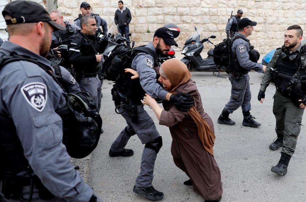 Palestinská žena se pokouší prorazit bariéru izraelské policie poté, co izraelské úřady uzavřely vchod na Chrámovou horu v Jeruzalémě.