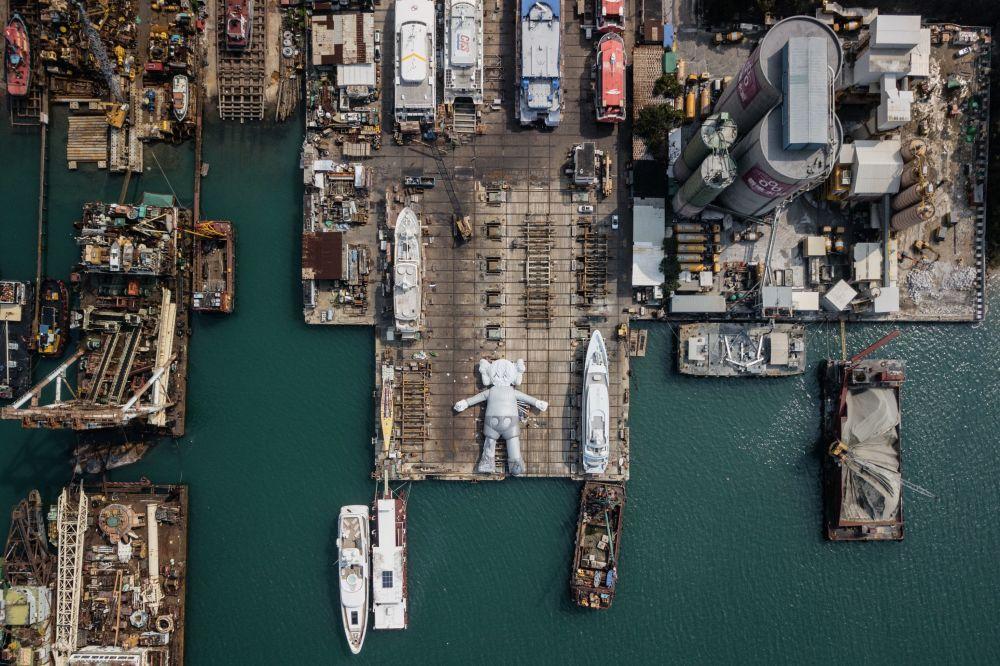 Socha KAWS: HOLIDAY od umělce a návrháře Briana Donnellyho v loděnici v Hongkongu.