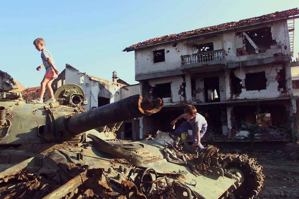Дети играют на разрушенном во время натовской бомбардировки сербском танке в югославском городе Клина, 1999 год