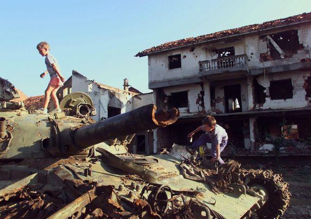 Děti si hrají na zničeném tanku, který byl zničen během bombardování NATO