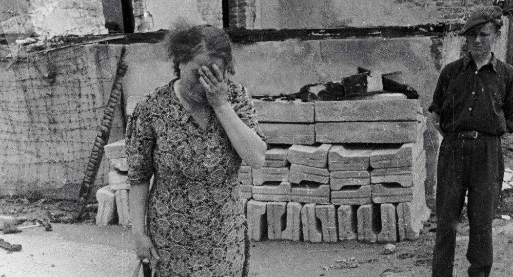 Žena plačící nad popelem lidí spálených v peci, německý koncentrační tábor Majdanek, Polsko