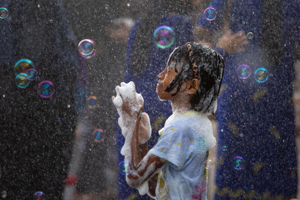 Dívka a mýdlové bubliny. Barmský novoroční Vodní Festival v Yangonu, Myanmar