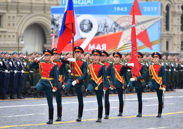 """Na píseň Alexandrova """"Svatá válka"""" vojáci praporu čestné stráže 154. samostatného velitelského Preobraženského pluku na Rudé náměstí přináší státní vlajku Ruské federace a prapor vítězství."""