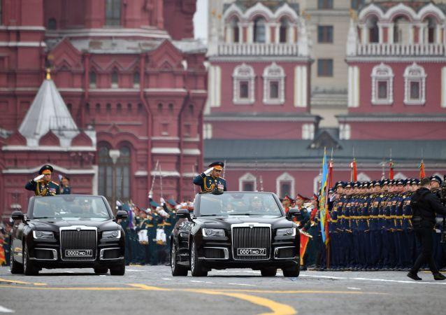 Před vojsky projíždí v kabrioletech ruské výroby Aurus, které se přehlídky účastní poprvé.