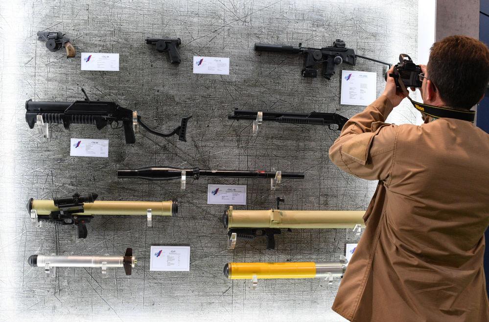 Návštěvník výstavy MILEX-2019 fotí stánek se zbraněmi