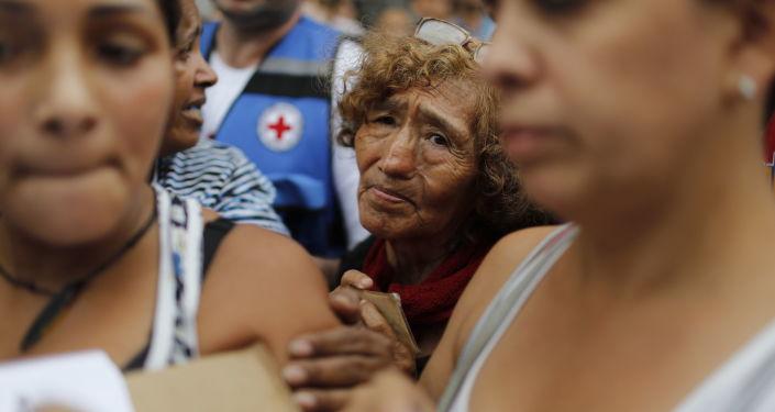 Obyvatelé v řadě pro prázdné kontejnery a tablety na čištění vody během akce Červeného kříže v Caracasu